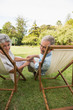 Smiling mature couple lying on sun loungers
