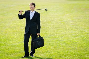 junger mann mit golfschläger und tasche