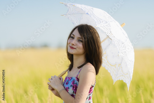 Beautiful sad and lonely woman with umbrella walking in wheat fi