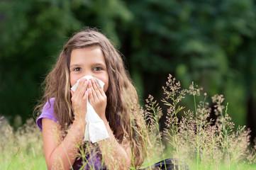 Kleines Mädchen mit Papiertaschentuch im Gras