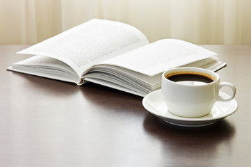 Cup of coffee and opened book on table against window