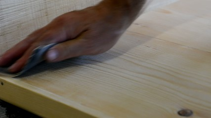Worker uses the emery paper to grind the wood.