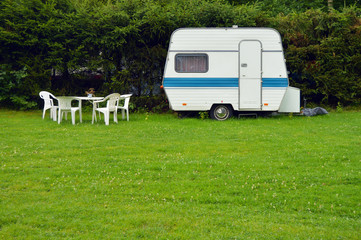 An old fashioned caravan with garden furniture