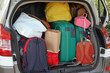 Car full of suitcases and bags to return from holidays