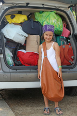 beautiful smiling girl with bag and suitcases in car