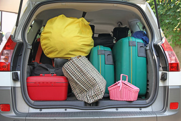 two green suitcases and many bags in the car