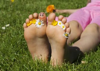 Kinderfüsse mit Gesicht und Blumen
