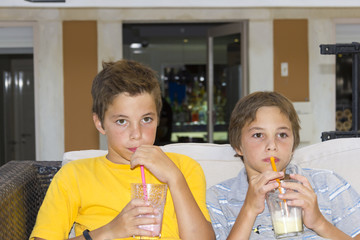 Adorable boys with glasses of milkshake