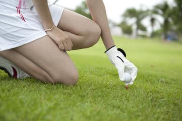 Hand lady placing golf ball on tee