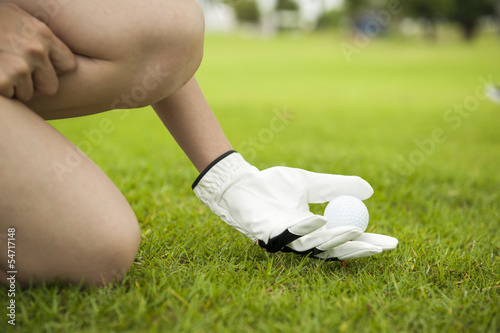 Hand lady placing golf ball on tee