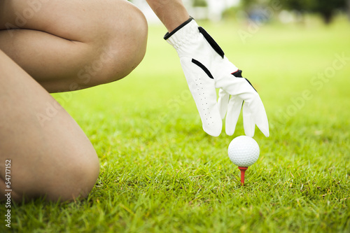 Lady placing golf ball on tee