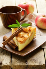 piece of homemade apple pie with cinnamon on a wooden table