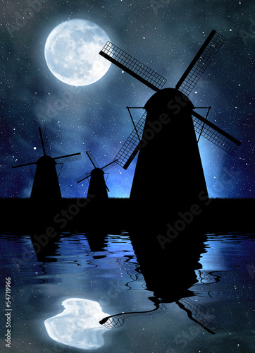Silhouettes of windmills on night sky with moon
