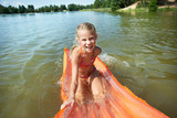 Joyful little girl on mattress in lake