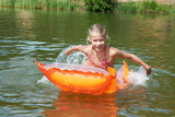 Happy little girl on orange mattress in lake