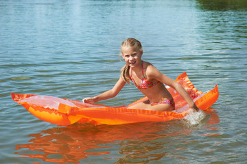 Happy little girl on mattress in lake