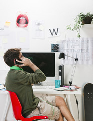 Young creative designer man at phone working at office.