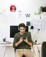 Young creative designer man at phone working at office