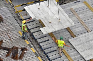 Ouvriers sur chantier reçoivent la plaque en béton de la grue