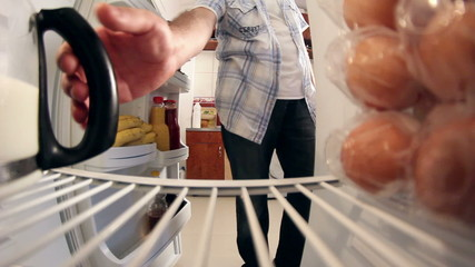 Man opening door of fridge to get milk and closes door