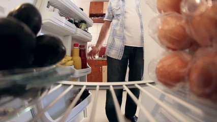 Man opening door of fridge to get fruits(plums) and closes door