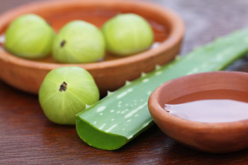 Fresh amla and aloe with small bowls