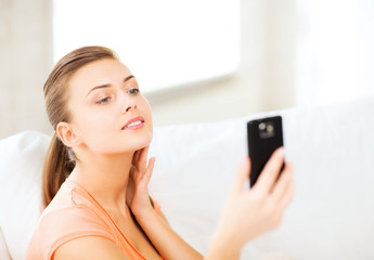 woman making self portrait with smartphone