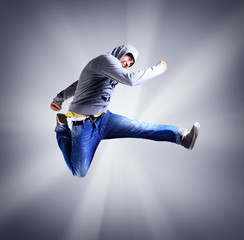 Portrait of an young man jumping in air against light background