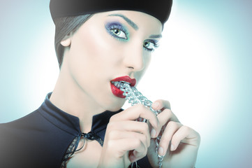 Dominant girl with turban on head, biting chain