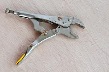 old metal locking pliers on wood background