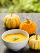 Pumpkin porridge and pumpkins on black wooden table and natural