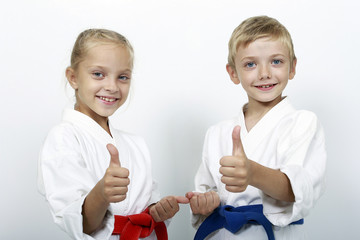 Children athletes with belts show a thumbs up