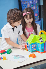 Boy And Girl Playing With Plastic House In Kindergarten