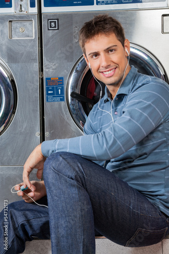 Man Listening To Music At Laundromat
