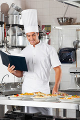 Chef With Checklist And Pasta Dishes At Counter