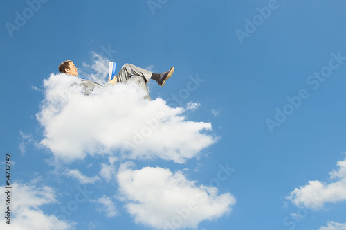 Businessman lying on clouds