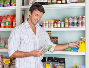 Man Selecting Food Packets In Store