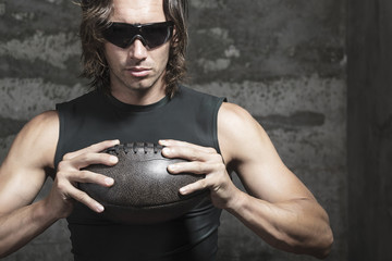 football player is  holding ball in hands