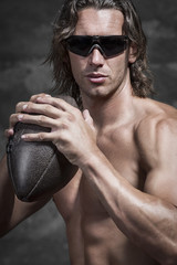 bare chested muscle man is holding american football ball
