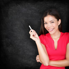 Teacher woman holding chalk by blackboard