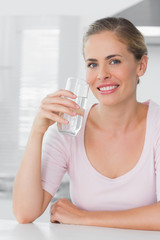 Cheerful woman holding glass of water