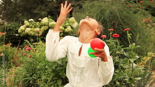 Young girl throws multicolored balls against flowers.
