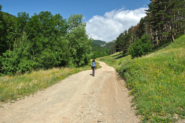 Winding dirt lane, mountain road with a trekking woman