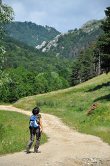 Winding dirt lane, mountain road with a trekking girl