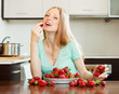 long-haired woman eating strawberry in home