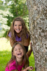 Zwei lachende Mädchen spielen verstecken hinter Baum