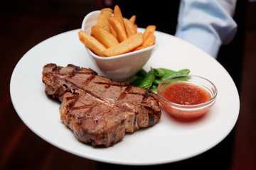 Waiter offering T-bone steak with french fries