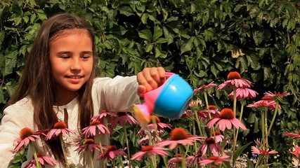 Young girl waters flowers.