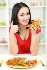 Girl with delicious pizza on kitchen background