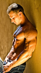 Handsome muscular male bodybuilder leaning against yellow wall